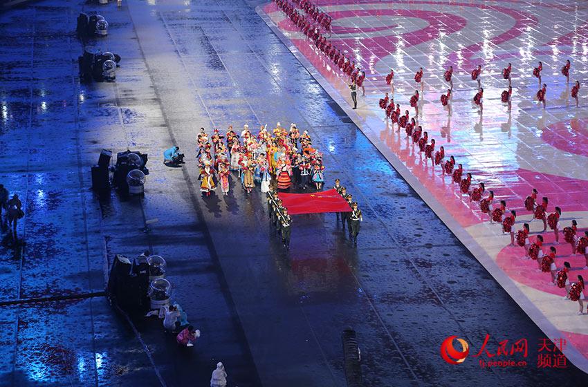 在鲜艳的五星红旗引领下,56个民族的兄弟姐妹手持鲜花携手同行。胡昱喆/摄